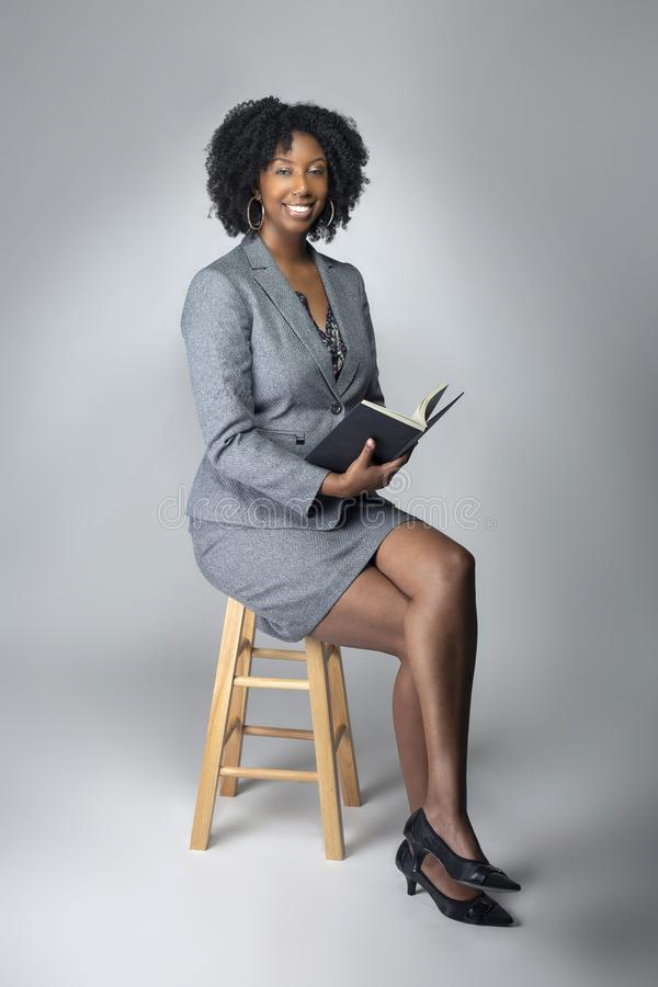 Black Female Author or Teacher in a Studio. Black female author posing with a book in a studio for a portrait.  She looks like a teacher or a writer.  The image stock image
