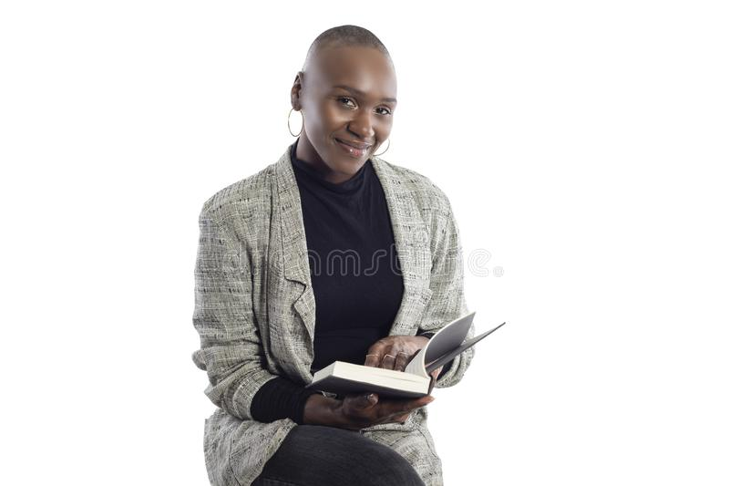 Black Female Author or Writer Posing with a Book. Black African American female author sitting with a book like she is about to be a keynote speaker on a seminar royalty free stock photos