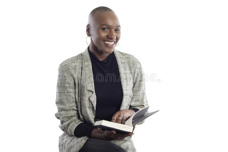 Black Female Author or Writer Posing with a Book. Black African American female author sitting with a book like she is about to be a keynote speaker on a seminar stock photo