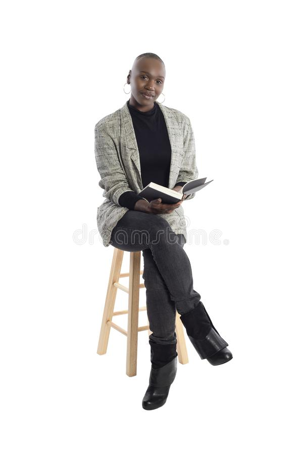Black Female Author or Writer Posing with a Book. Black African American female author sitting with a book like she is about to be a keynote speaker on a seminar royalty free stock photo