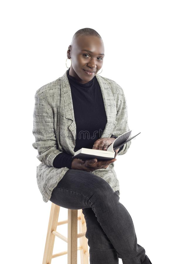 Black Female Author or Writer Posing with a Book. Black African American female author sitting with a book like she is about to be a keynote speaker on a seminar stock image