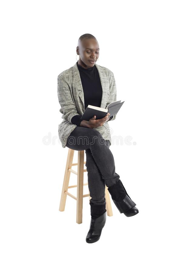 Black Female Author or Writer Posing with a Book. Black African American female author sitting with a book like she is about to be a keynote speaker on a seminar royalty free stock images