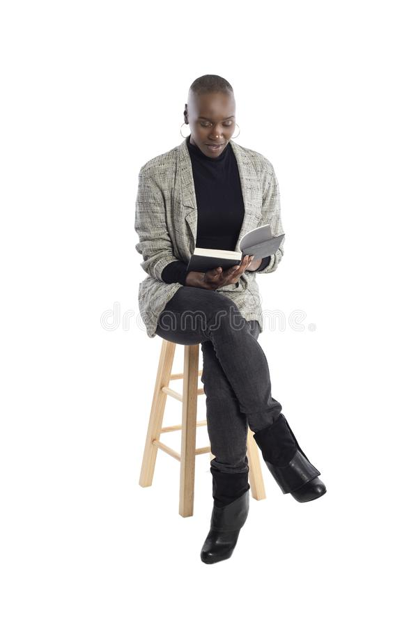 Black Female Author or Writer Posing with a Book. Black African American female author sitting with a book like she is about to be a keynote speaker on a seminar stock images