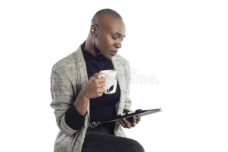 Black Female Author or Writer Posing with a Tablet and Coffee. Black African American businesswoman or writer as a keynote speaker for a seminar preparing for royalty free stock photos