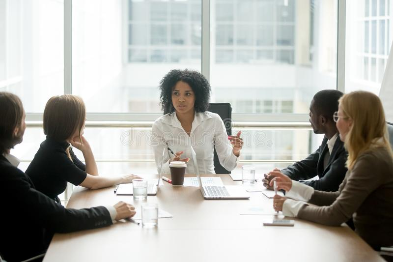 Black female boss leading corporate meeting talking to diverse b. Black female boss leading corporate multiracial team meeting talking to diverse businesspeople stock photography