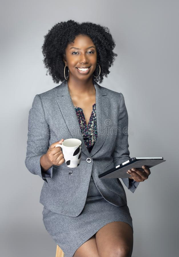 Black Female Businesswoman Keynote Speaker Posing with a Tablet and Coffee. Black African American businesswoman or writer as a keynote speaker for a seminar royalty free stock image