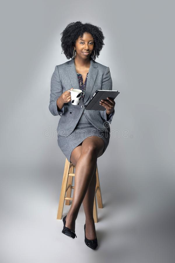 Black Female Businesswoman Keynote Speaker Posing with a Tablet and Coffee. Black African American businesswoman or writer as a keynote speaker for a seminar royalty free stock images