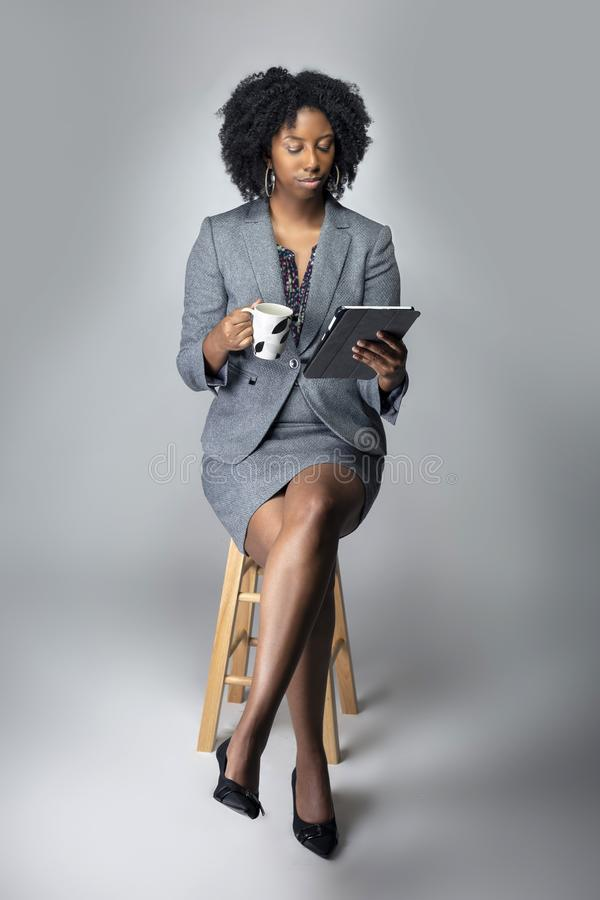 Black Female Businesswoman Keynote Speaker Posing with a Tablet and Coffee. Black African American businesswoman or writer as a keynote speaker for a seminar royalty free stock photos
