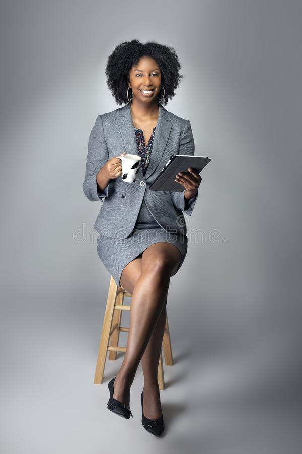 Black Female Businesswoman Keynote Speaker Posing with a Tablet and Coffee. Black African American businesswoman or writer as a keynote speaker for a seminar stock image