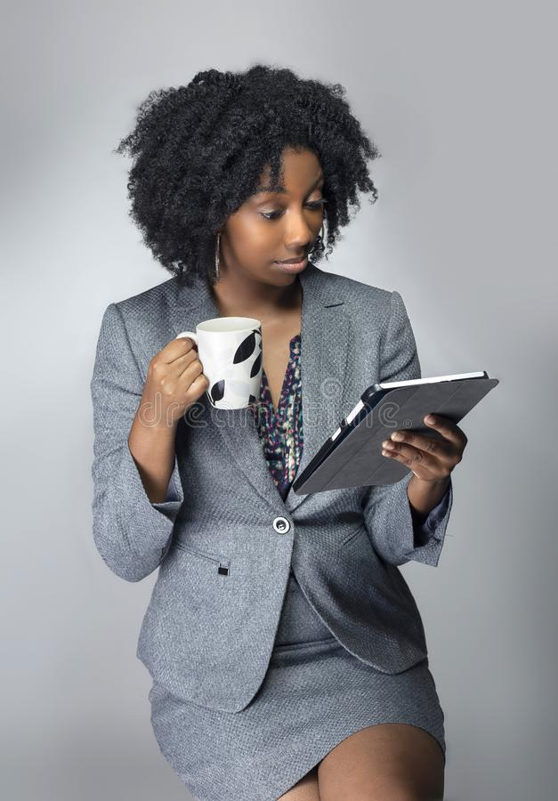 Black Female Businesswoman Keynote Speaker Posing with a Tablet and Coffee. Black African American businesswoman or writer as a keynote speaker for a seminar stock images