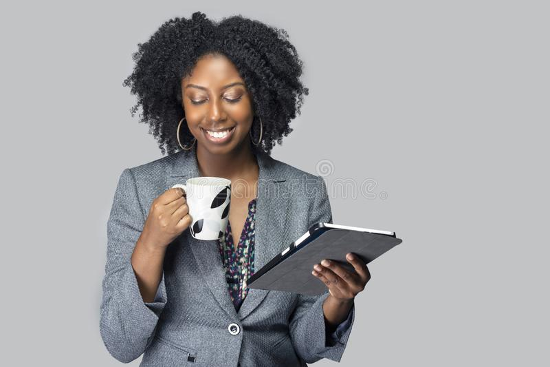Black Female Businesswoman Keynote Speaker Posing with a Tablet and Coffee. Black African American businesswoman or writer as a keynote speaker for a seminar royalty free stock photography