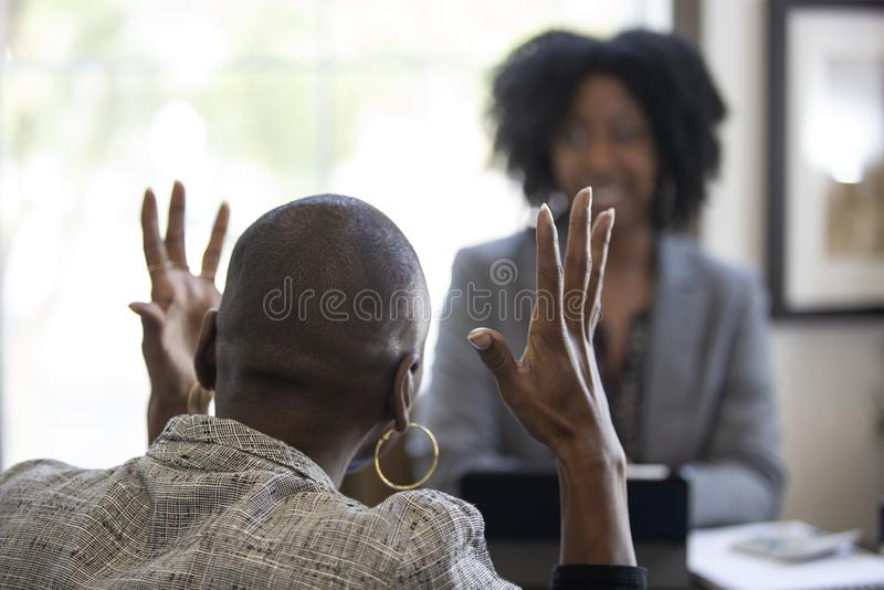 Black Female Client Angry at Tax CPA Accountant. Black female client is upset at tax preparer or CPA accountant in an office. The image can also depict a manager royalty free stock images