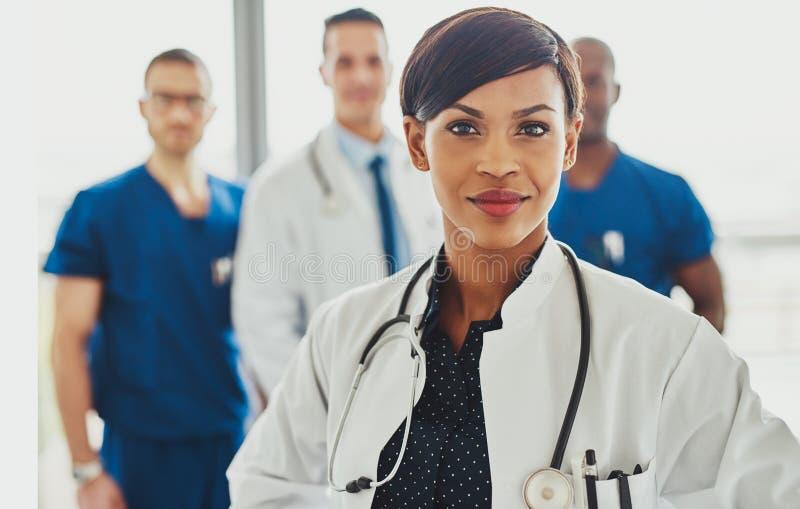 Black female doctor leading medical team stock photography