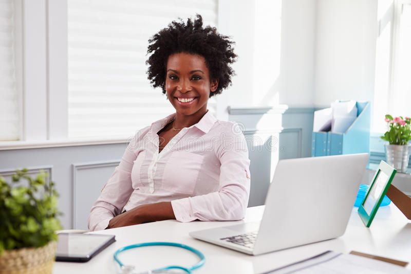 Black female doctor sits at an office desk looking to camera royalty free stock images