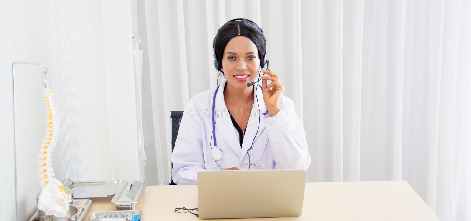 Black female doctor,specialist with sitting desk and headset, consulting health care and disease counseling to patients and public. Online communication from stock photo