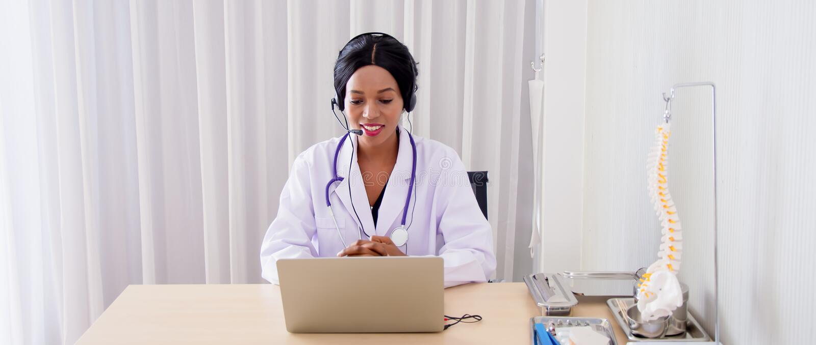 Black female doctor,specialist with sitting desk and headset, consulting health care and disease counseling to patients and public. Online communication from royalty free stock photo