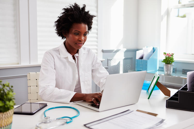 Black female doctor wearing white coat at work in an office stock photo