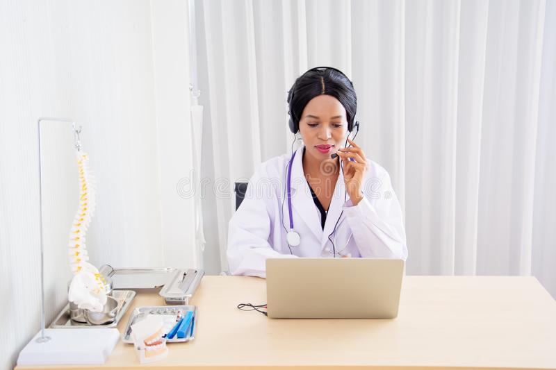 Black female doctors, specialist sitting at desk with headset, consulting health care and disease counseling to patients and the. Public, with online stock images