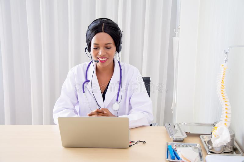 Black female doctors, specialist sitting at desk with headset, consulting health care and disease counseling to patients and the. Public, with online stock image