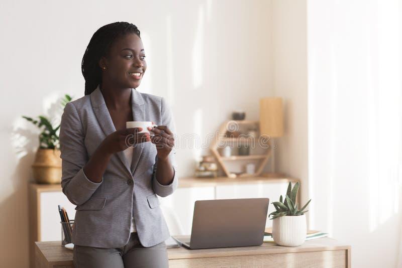 Black female employee drinking coffee in office, having break in work royalty free stock photo