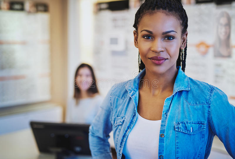 Black female entrepreneur. In her store looking at camera, colleague in background royalty free stock photography