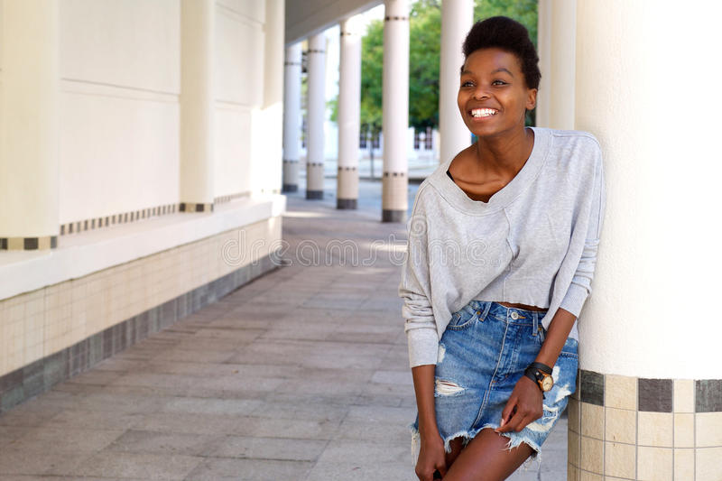 Black female fashion model standing outdoors and smiling stock photo