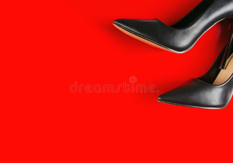 Black female high heel shoes. On red background, top view royalty free stock photos