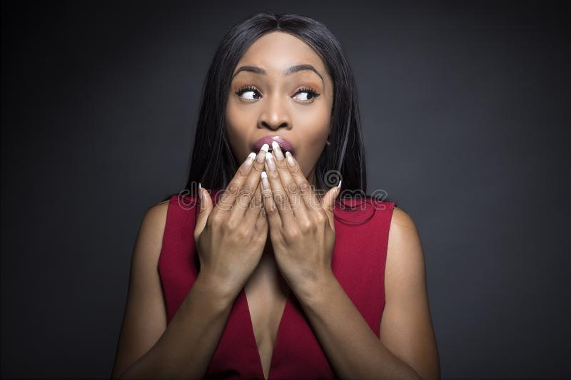 Black Female with Shocked Expressions. Black female model on a dark background with shocked and surprised expressions royalty free stock photo
