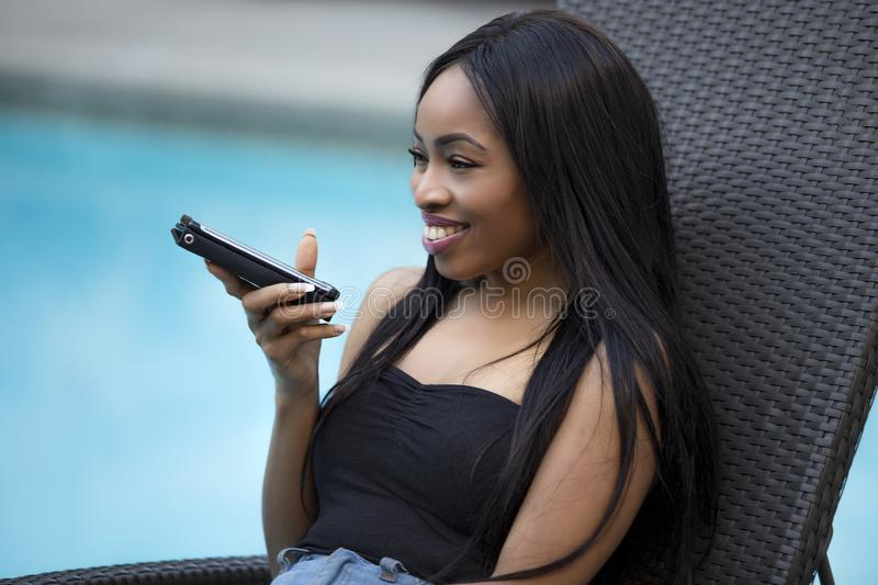 Female on a Vacation using a Voice Assistant on a Smart Phone. Black female on a speaker phone call in a hotel resort. She is working while on vacation or royalty free stock photos