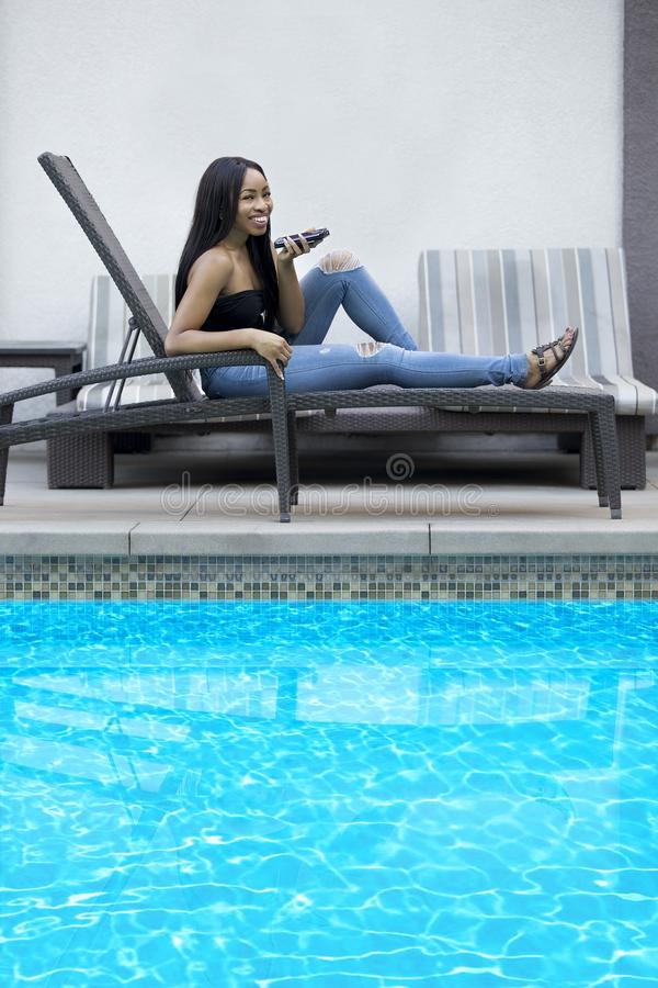 Using Cell Phone to Dictate Reminders While on Vacation. Black female on a speaker phone call in a hotel resort. She is working while on vacation or dictating royalty free stock photos