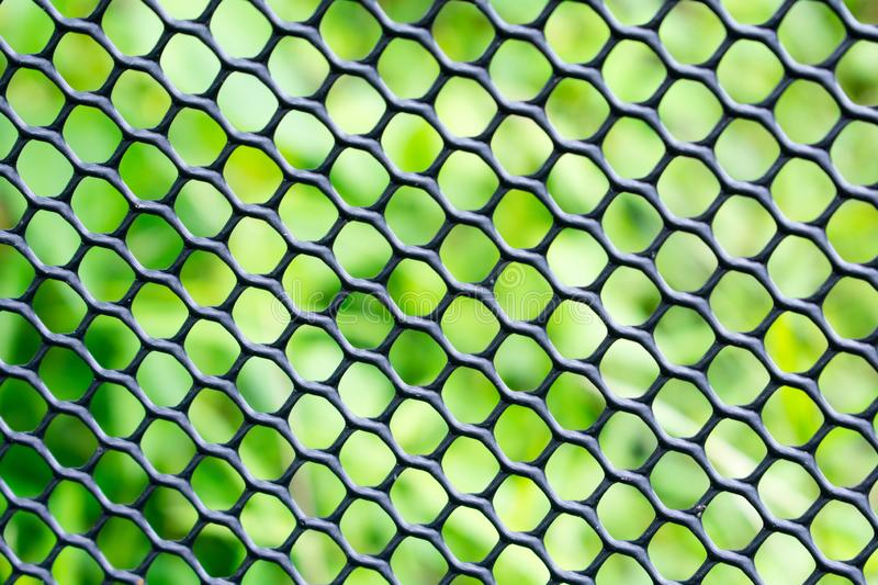 Black fence close up with green background, texture background. With circle hole royalty free stock photos