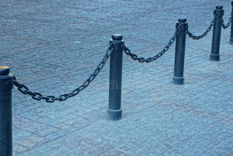 Black fence with iron chains and pillars on the sidewalk on the city street. Part of a black fence with iron chains and pillars on a gray stone pavement on a royalty free stock images