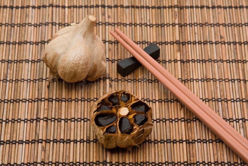 Black fermented garlic. Whole and cut bulb of black fermented garlic stock photo