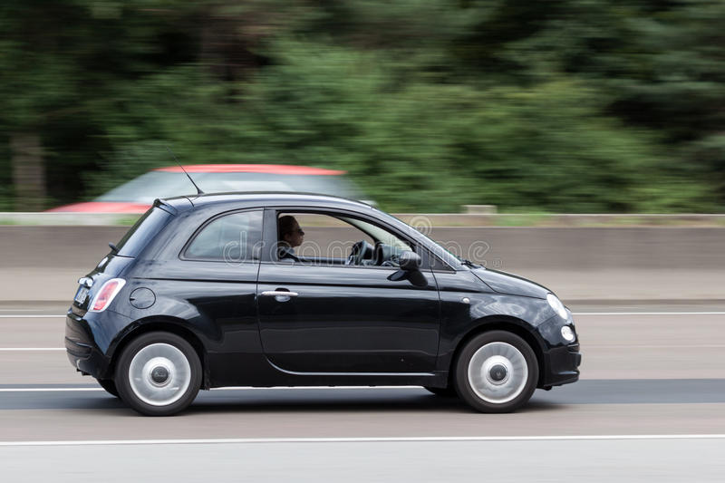 Black Fiat 500 on the highway. FRANKFURT, GERMANY - JULY 26: Black Fiat 500 supermini car moving fast on the highway A5 near Frankfurt. July 26, 2015 in royalty free stock photography
