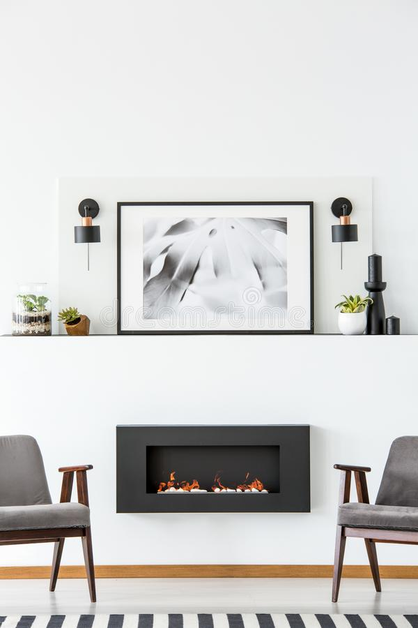 Black fireplace between grey armchairs in white flat interior wi. Th poster between lamps. Real photo stock image