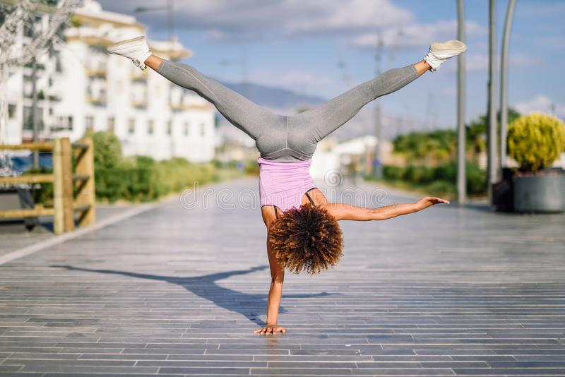 Black fit woman doing fitness acrobatics in urban background royalty free stock photography