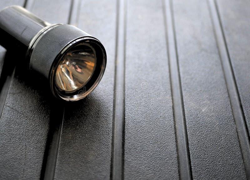 Black flashlight on rugged background. Black flashlight for camping on rugged background royalty free stock images