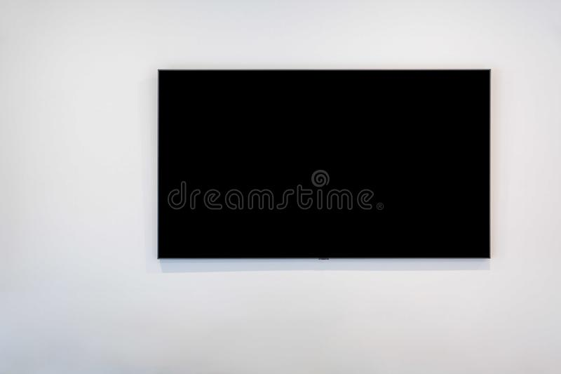 Black flat screen TV on white wall. royalty free stock images