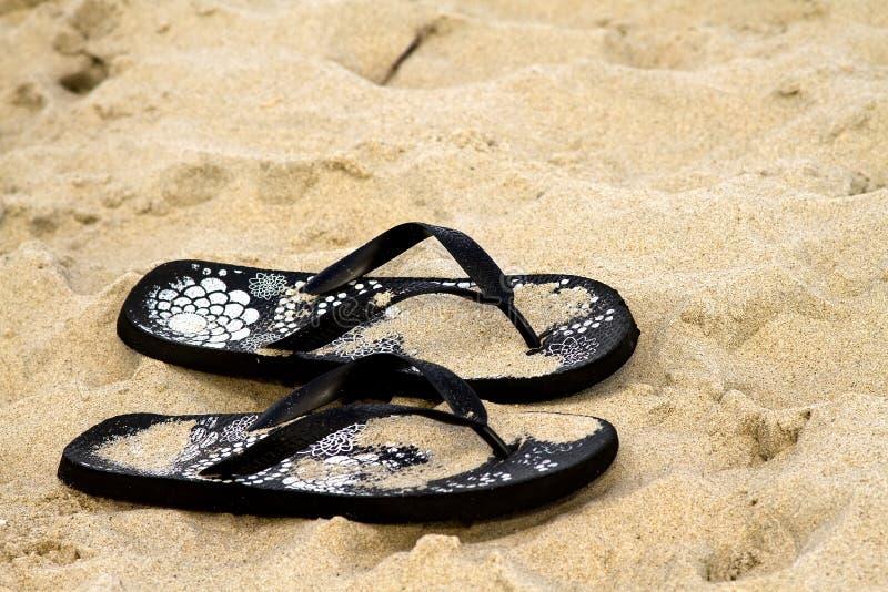 Black Flip Flops in Sand. Pair of black flip flops in sand at beach stock images
