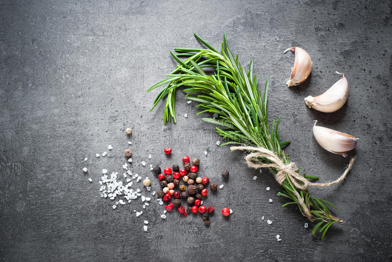 Black food background with olive oil and spices. Black food background with olive oil, rosemary and spices, copy space, top view royalty free stock images