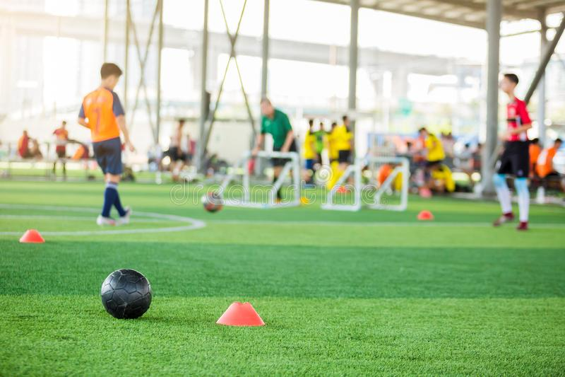 Black football on green artificial turf with marker cone blurry soccer team training. Blurry boy soccer player jogging between marker cones and control ball royalty free stock image