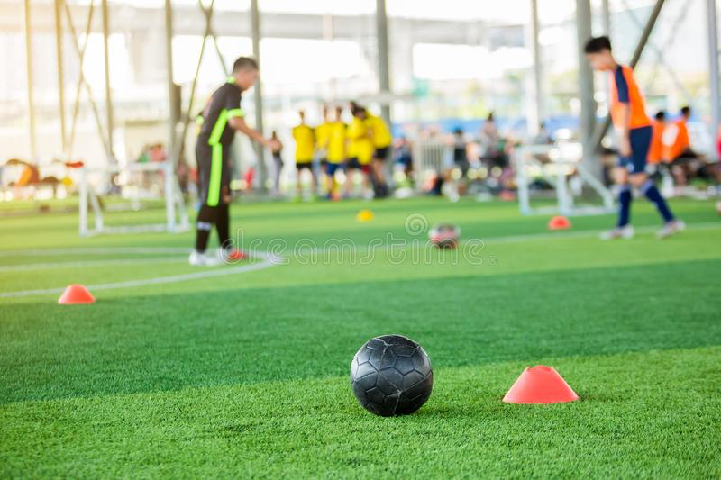 Black football on green artificial turf with marker cone blurry soccer team training. Blurry boy soccer player jogging between marker cones and control ball stock photo