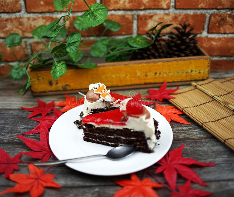 Black forest cake and wood table with maple leaf royalty free stock image