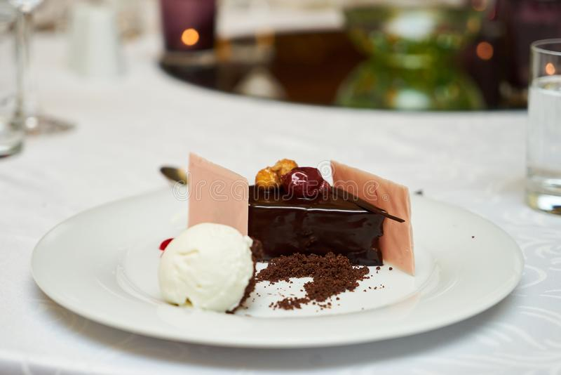 Black forest slice cake with cherry. Vanilla ice-cream, chocolate dirt on a white plate, close-up. Tradidional delicious sweet dessert food royalty free stock photo