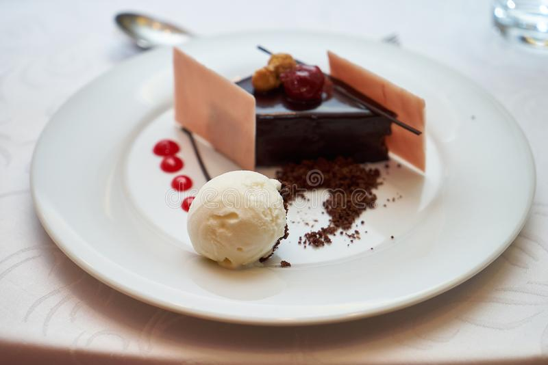 Black forest slice cake with cherry. Vanilla ice-cream, chocolate dirt on a white plate, close-up. Tradidional delicious sweet dessert food stock image