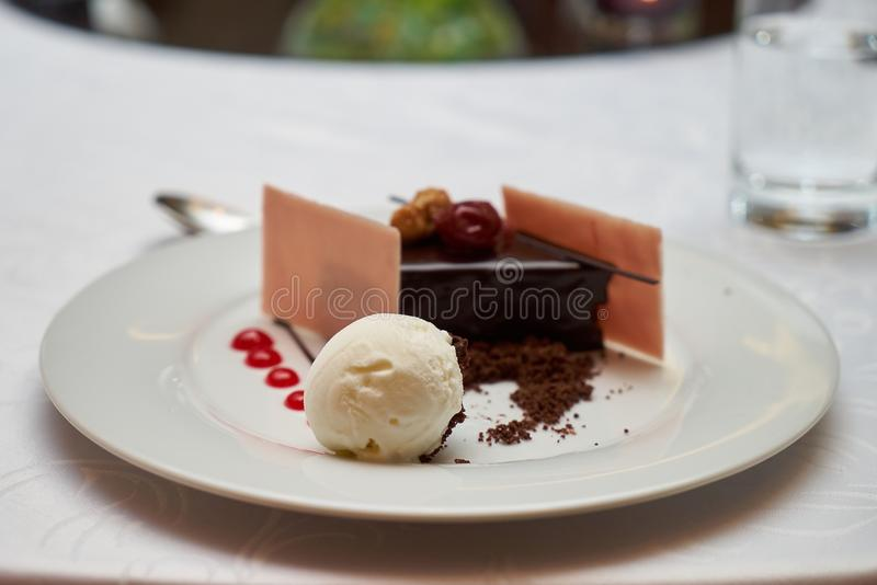 Black forest slice cake with cherry. Vanilla ice-cream, chocolate dirt on a white plate, close-up. Tradidional delicious sweet dessert food stock photography