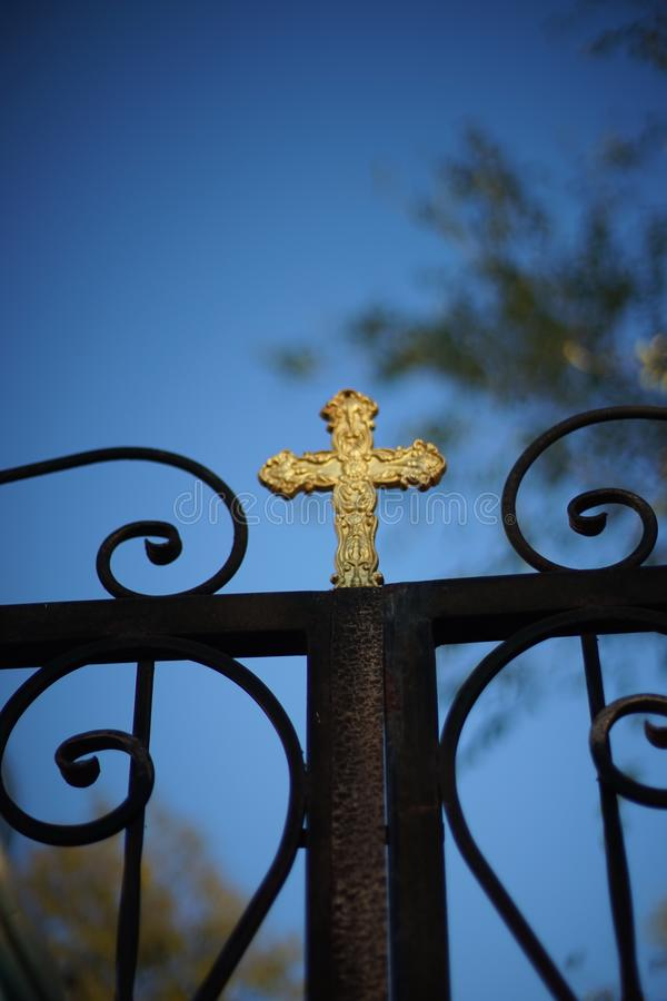 Black forged fence with a golden cross royalty free stock photography