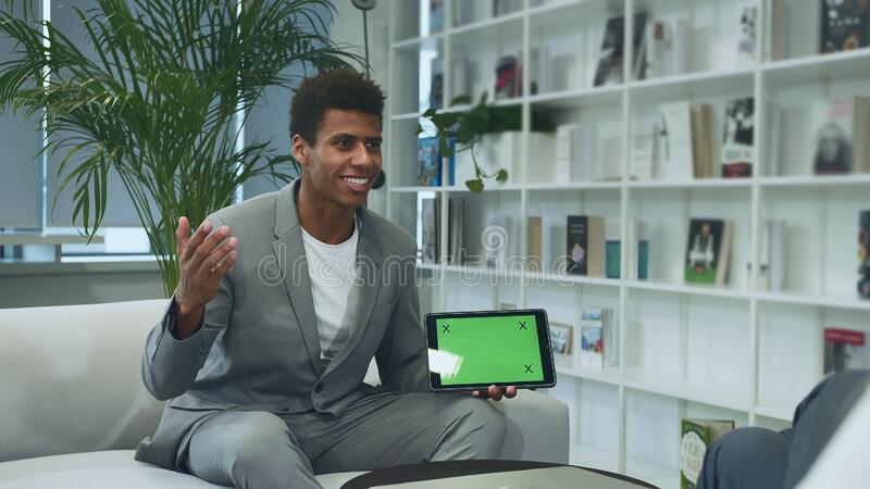 Black formal man making presentation with tablet with green chromakey screen. Young African-American man in suit sitting. Young African-American man in suit royalty free stock images