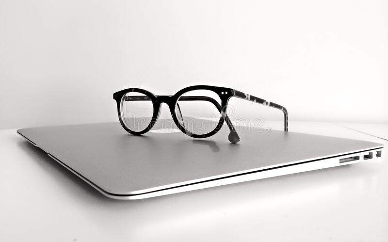 Black Frame Eyeglasses on Silver Macbook Air stock image
