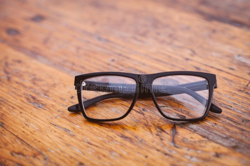 Black Frame Wayfarer Eyeglasses on Brown Wooden Surface stock photo